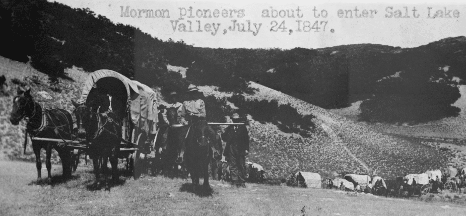 Pioneer Day by popular US online genealogists, Price Genealogy: black and white image of a covered wagon train.
